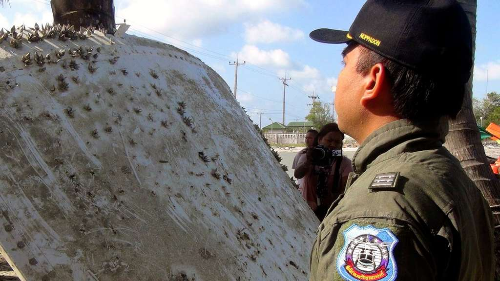 epa05122806 A Thai Royal Air Force officer inspects a piece of suspected airplane wreckage at a beach in Pak Phanang district, Nakhon Si Thammarat province, southern Thailand, 24 January 2016. A piece of wreckage found on a beach in eastern Thailand prompted authorities to investigate whether it was part of missing Malaysia Airlines flight MH370, while experts said it was likely part of another craft. EPA/STR THAILAND OUT +++(c) dpa - Bildfunk+++